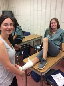 Two campers pose for photo during ankle wrapping activity while one camper wraps the ankle of the other camper