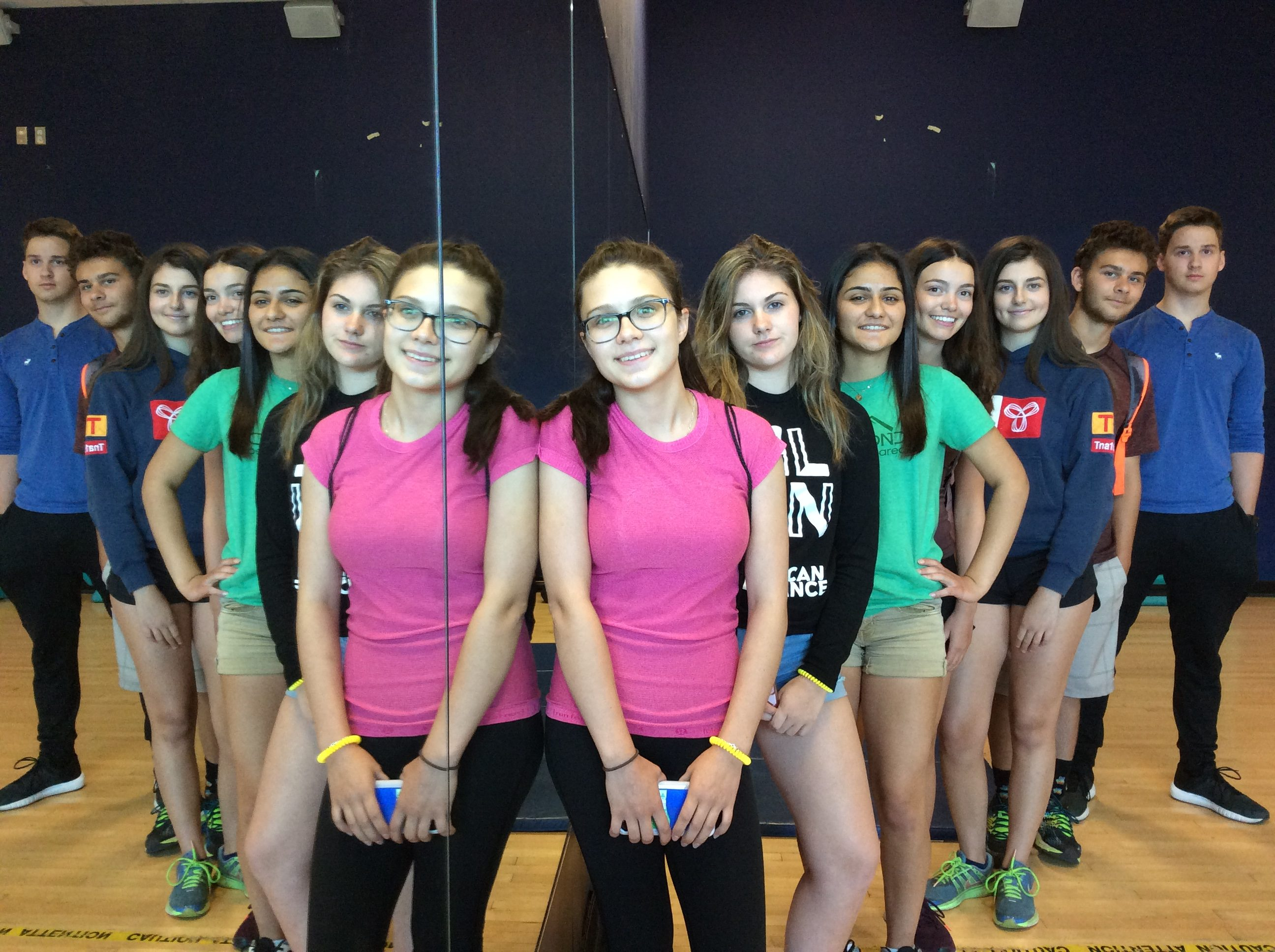 Campers pose in staggered line beside mirror in wellness class; staggered line is reflected in mirror to give illusion of two lines of people
