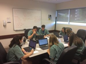 Camper group sitting at table using laptops for case study activity