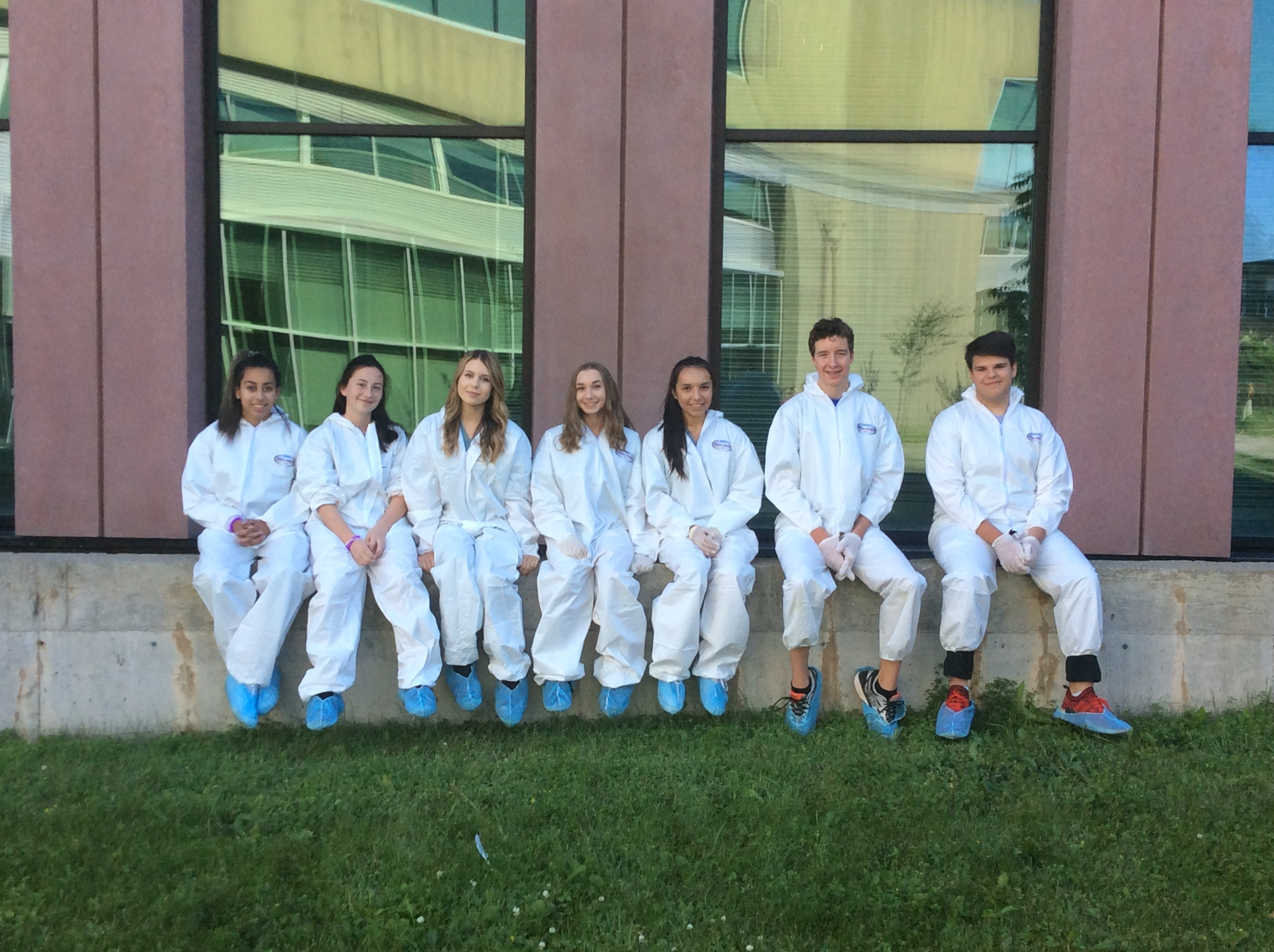 Camper group poses for photo while sitting on a cement retaining wall wearing white painter's coveralls and blue booties