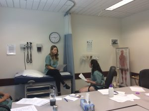Two campers practice clinical interviewing skills; one camper sits on exam bed while other camper sits on chair