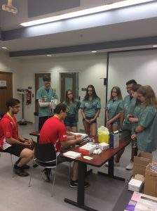Two team leads sit at table and demonstrate IV insertion activity to campers standing around the table