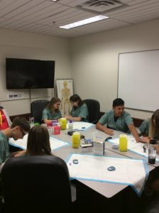 Camper group sits at table in small group room and practices glucose testing