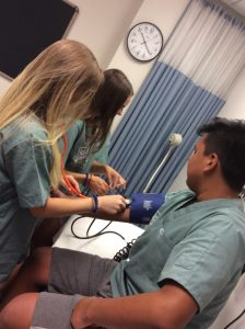 Two campers use stethescope and blood pressue cuff to take blood pressure of fellow camper
