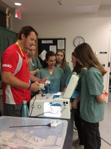Team lead demonstrates laproscopic surgery simulator to campers