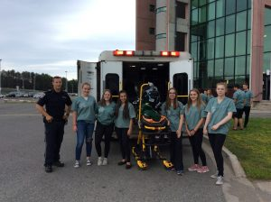 Camper group and paramedic pose for photo with EMS stretcher in front of ambulance