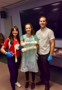 Camper displays arm casts with team lead and Physician Assistant