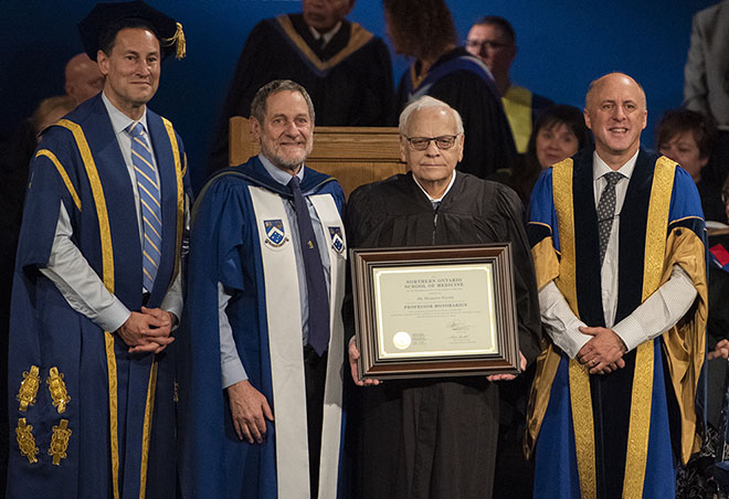 Photo of Dr. Hermann Falter receiving an award during a graduation ceremony. Pictured, left to right, Steve Paikin, Chancellor, Laurentian University; Dr. Roger Strasser, NOSM Dean and CEO; Dr. Hermann Falter; and, Dr. Pierre Zundel, Interim President and Vice-Chancellor, Laurentian University.