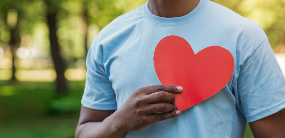 black-man-holding-red-heart-on-his-chest-picture-id1145183163