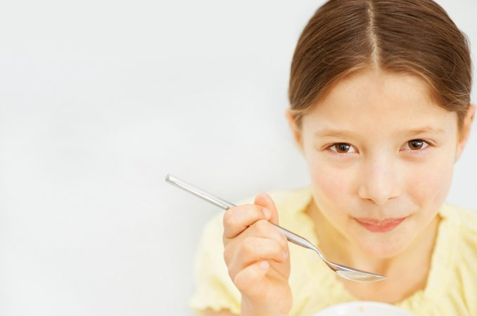 Closeup of a little girl eating cereals against white looking to camera.